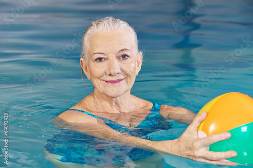 Senior woman with water ball in pool