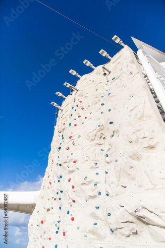 Rock Climbing Wall Under Blue Sky with Bell at Top