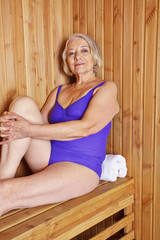 Old woman sitting in sauna