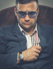 Frowning businessman wearing sunglasses