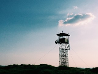 lookout tower silhouette against blue sky