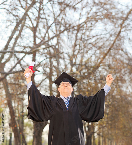 Happy mature graduate holding diploma outdoors