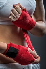 Boxing woman binds the bandage on his hand