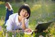 Beautiful asian student using laptop outdoor