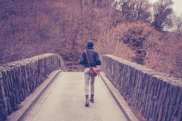 Young woman crossing bridge in forest