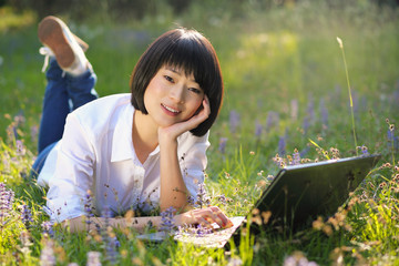 Beautiful asian student using laptop outdoor