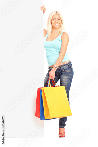 Woman holding shopping bags behind blank panel
