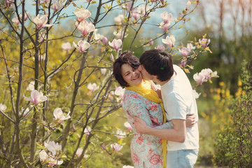 girl hugging a guy in the park flowering magnolias