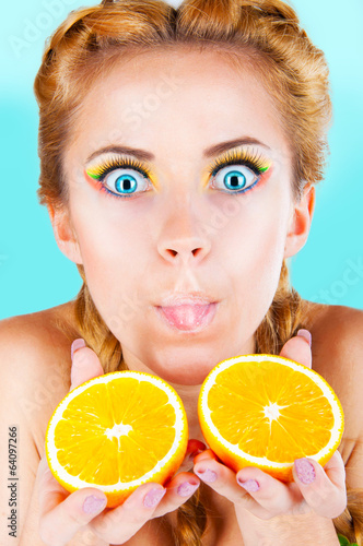 beautiful woman shows the two halves of the orange