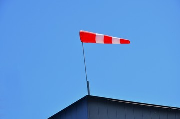 A bright red windsock atop a building