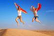 Happy women jumping in the desert