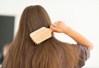 Young woman combing hair in bathroom. rear view