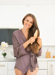 Happy young woman combing hair in bathroom
