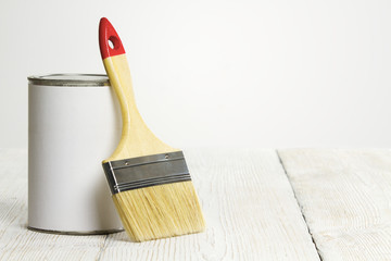 Paintbrush and can, paint brush and white color wooden floor