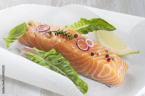 fresh salmon filet with vegetable ready to cook on parchment