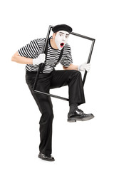Male mime artist walking through a metal frame