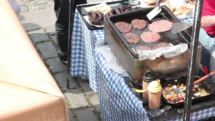 Middle aged caucasian man frying meat for hamburger at local far