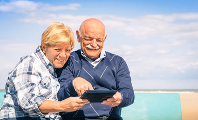 Senior happy couple having fun with a tablet at the beach