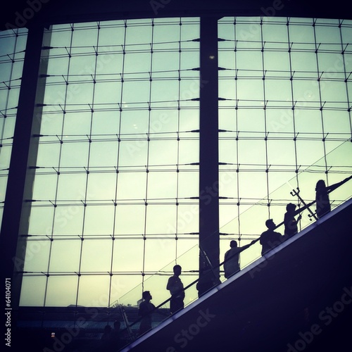 silhouettes man going up by escalator