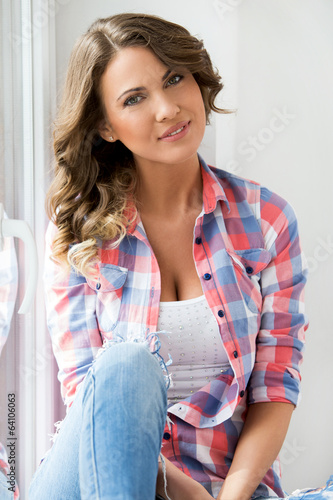 Lifestyle. Beautiful girl by the window