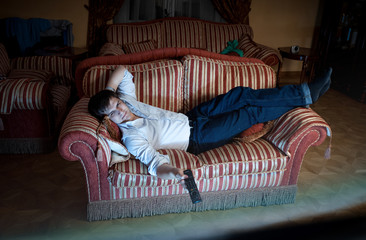 man switching TV channels on sofa at night