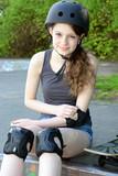 Teenager mit Skateboard legt Protektoren an