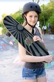 Teenager mit Skateboard trägt Helm
