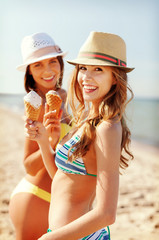 girls in bikinis with ice cream on the beach