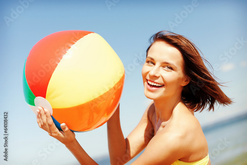 girl in bikini playing ball on the beach