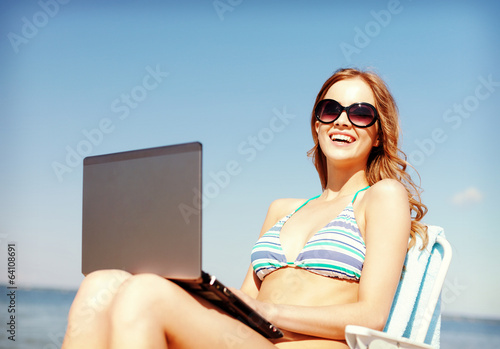 girl looking at tablet pc on the beach