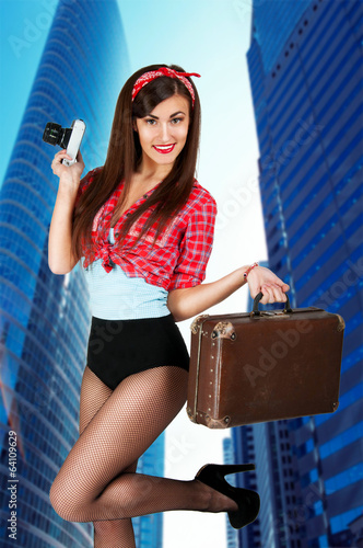 sexy woman with a suitcase and a camera