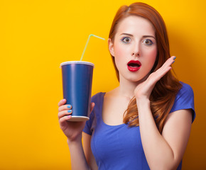 Redhead girl with drink on yellow background.