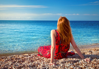 young girl sitting on the beach and looking at the sea