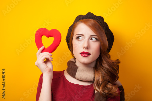 Redhead girl with shape heart on yellow background.