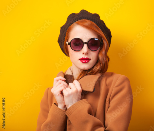 Redhead women in beret on yellow background.