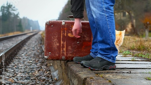 Man with a suitcase on the platform playing with the cat
