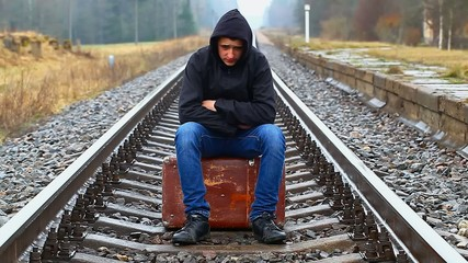 .Nervous teenage boy with a suitcase on the railway episode 2