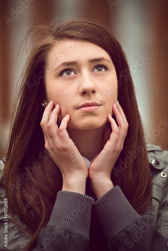 Thoughtful young woman sitting daydreaming