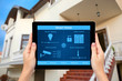 Female hands hold a tablet with system smart house on the backgr - 64114040