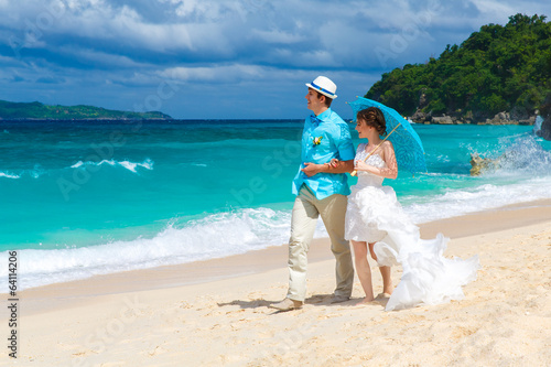 bride and groom walk along the tropical coast with blue umbrella