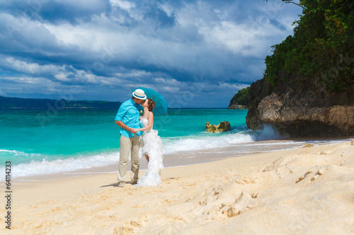 bride and groom with blue umbrella kiss on the tropical coast