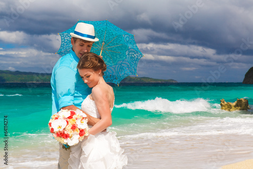 happy bride and groom with blue umbrella and wedding bouquets on
