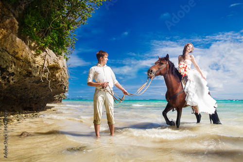 bride and groom walking with horse on a tropical beach