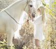 Blonde beautiful woman touching mejestic horse
