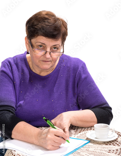 Mature woman writing documents with cup of coffee