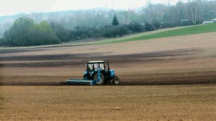 Traktor plows the land in spring