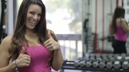 Smiling sportswoman waving at camera. Gym
