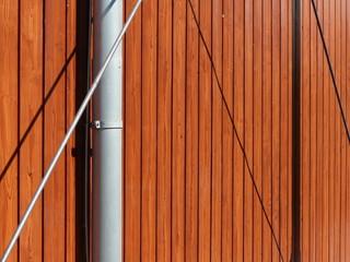 Silberne Verstrebung und Regenrohr vor braunem Holz