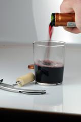Rotwein in Glas eingießen