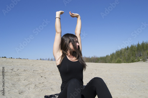 Beautiful woman with raised arms (stretching, beach)